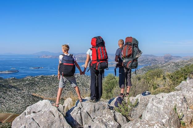 Een sportieve familie met grote rugzakken staat op een rots en kijkt naar het prachtige uitzicht over de middellandse zee