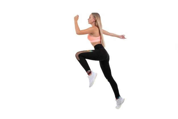 Een sportieve jonge vrouw in een roze top, legging en gympen doet oefeningen