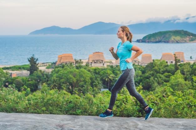 Een sportieve jonge vrouw rent tegen de zee aan.