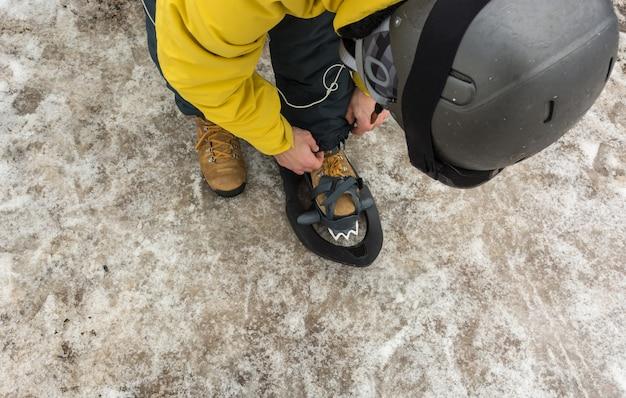 Een sportieve man die zijn sneeuwschoenen aantrekt om een besneeuwde bergtocht te beginnen.