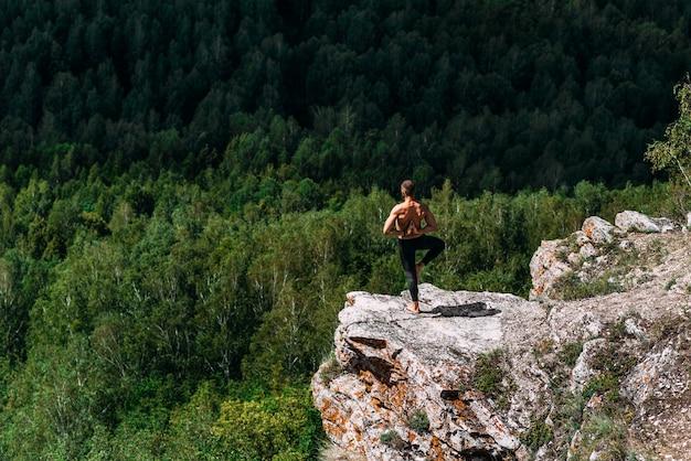 Een sportieve man doet yoga. een gezonde leefstijl. de concentratie van het lichaam. een man doet yoga in de bergen. een man doet yoga op een rots. een man mediteert in de natuur. meditatie in de bergen