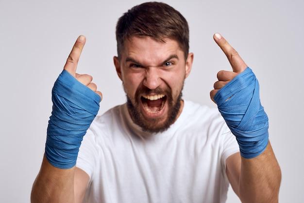 Een sportieve man in een wit t-shirt boksbandages op zijn handen blazen oefeningen oefenen