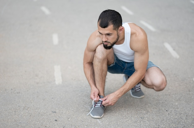 Een sportieve man knoopt de veters van zijn sneakers voordat hij over straat rent