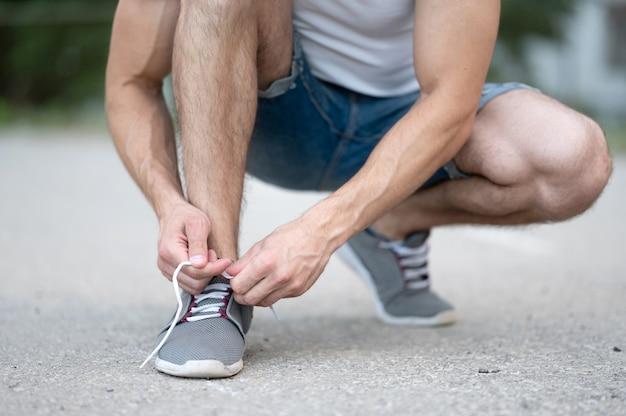 Een sportieve man knoopt de veters van zijn sneakers voordat hij van dichtbij over straat rent
