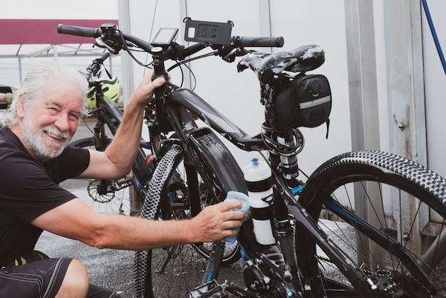 Een sportieve senior man wast de fietsen met zeep en spons bij het tankstation