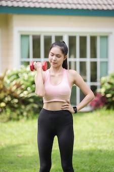 Een sportieve vrouw in sportkleding oefent in de tuin voor haar huis