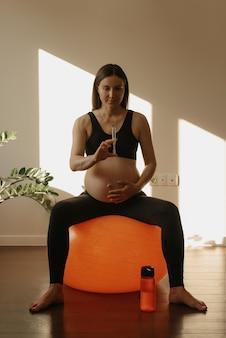 Een sportieve zwangere vrouw zit op een oranje oefenbal en controleert thuis een spuit met vitamines. gezonde fit zwangerschap.