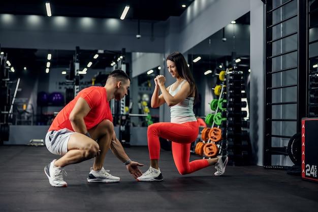 Een sportinstructeur traint een gemotiveerde vrouwelijke glimlachende persoon in de sportschool met trainingsapparatuur