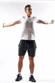 Een sportman in korte broek en een t-shirt op een lichte achtergrond gebaart met zijn handen.