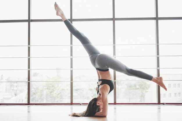 Een sportvrouw die yogalessen volgt en haar benen strekt bij het grote raam