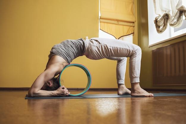 Een sportvrouw voert myofasciale massage van rugspieren uit met behulp van een cirkel voor yoga-preventie van overbelasting van de rug
