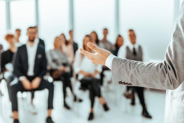 Een spreker die voor luisteraars in een vergaderruimte staat