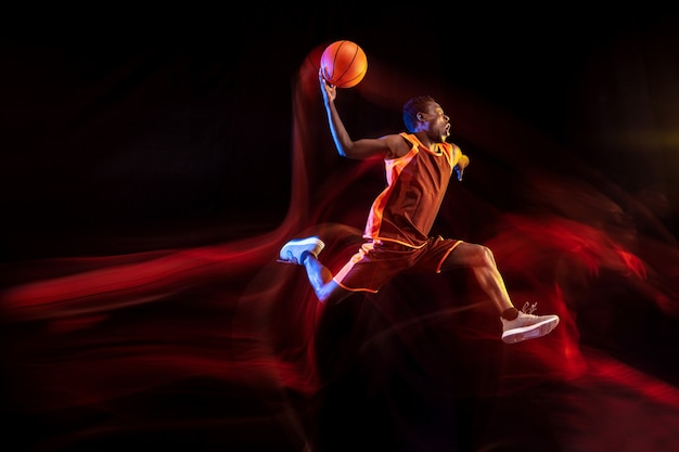 Een sprong voor het winnen. afro-amerikaanse jonge basketbalspeler van rood team in actie en neonlichten over donkere studioachtergrond. concept van sport, beweging, energie, dynamische, gezonde levensstijl.