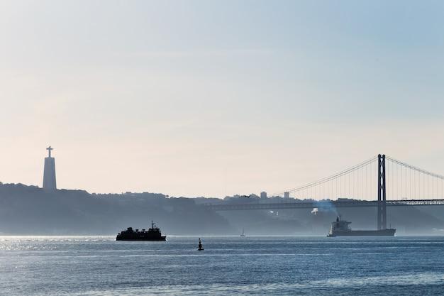 Een stad aan de oevers van de rivier de taag en silhouet van het monument.