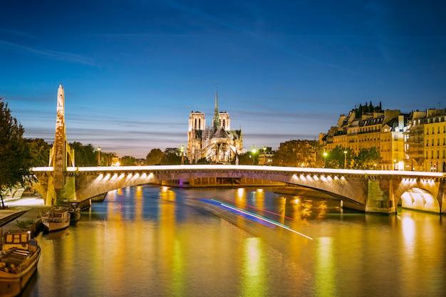 Een stadsgezicht van parijs met notre-dame en bruggen in de avond, frankrijk