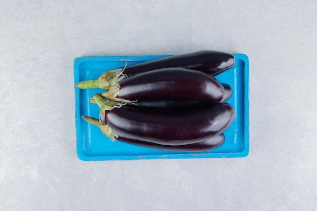 Een stapel aubergines op een dienblad op het marmeren oppervlak