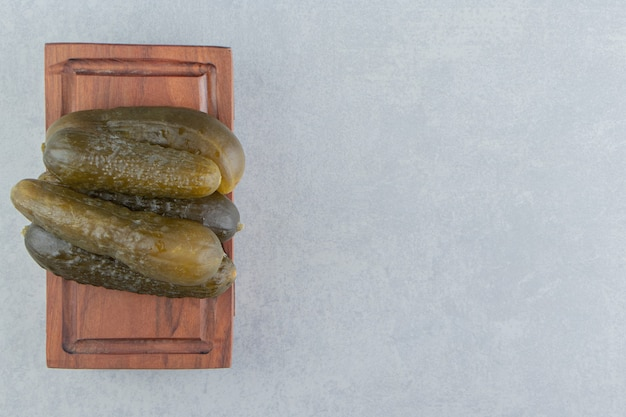 Een stapel augurken komkommer op een bord, op het marmeren oppervlak