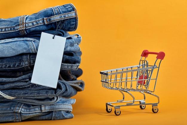 Een stapel blauwe spijkerbroek met een witte lege tag op een gele achtergrond winkelen trolley verkoop consept hoop stijlvolle trendy denim broek