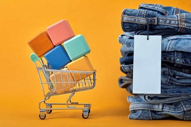 Een stapel blauwe spijkerbroek met een witte lege tag op een gele achtergrond