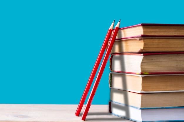 Een stapel boeken en twee rode houten potloden op een blauw, trappen, klimmende boeken, kennis vergaren, terug naar school