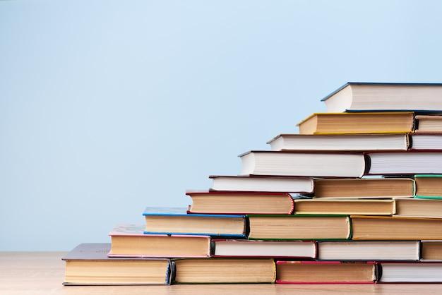Een stapel boeken in de vorm van een ladder, staat op een houten tafel tegen een lichtblauwe muur