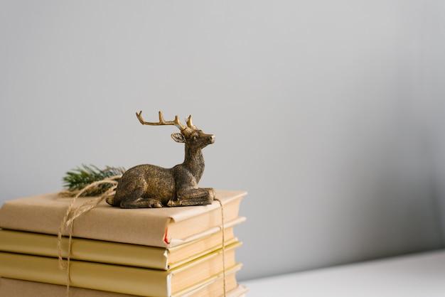 Een stapel boeken in kraandocument en een beeldje van een zittend hert op een grijze achtergrond. copyspace