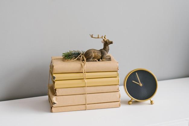 Een stapel boeken in kraanpapier, gebonden met touw, het is een beeldje van een zittend hert dat naast een bureauklok staat