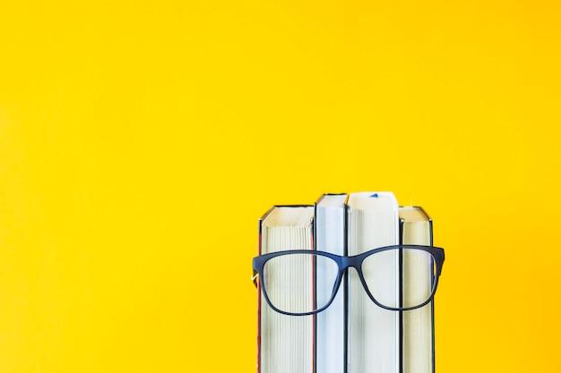 Een stapel boeken met een bril is een afbeelding van iemands gezicht