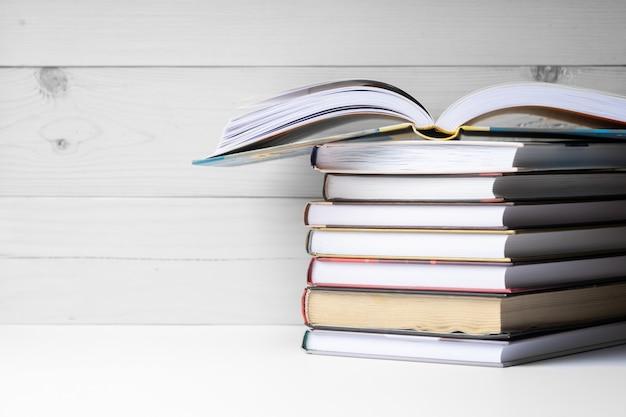 Een stapel boeken op een houten achtergrond.