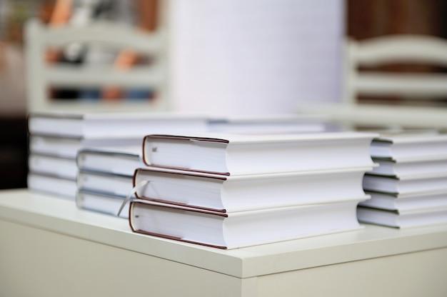Een stapel boeken op een witte tafel