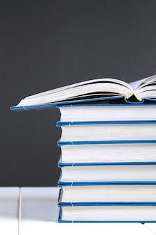 Een stapel boeken op schoolbordachtergrond. een verborgen boek bovenop de stapel.