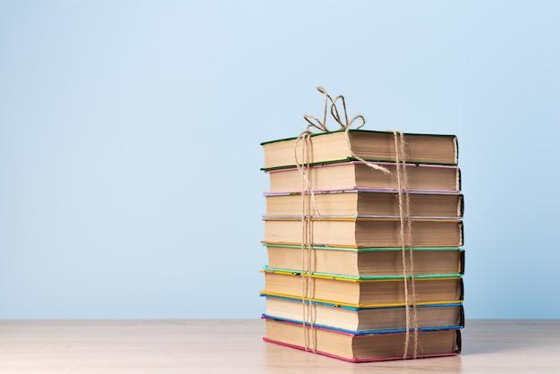 Een stapel boeken vastgebonden met een touw staat op een houten tafel tegen een lichtblauwe muur