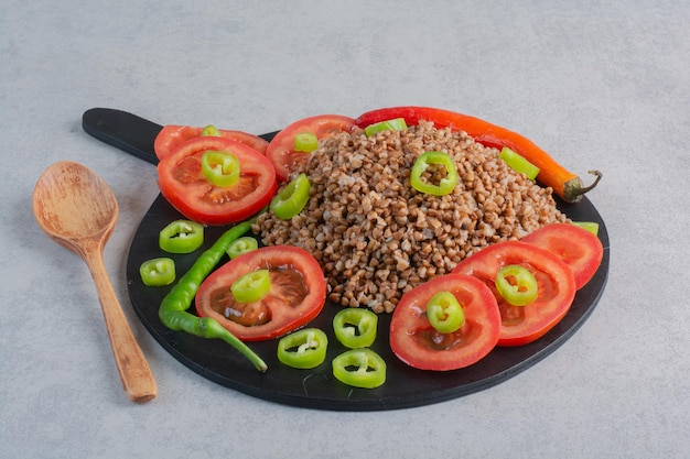 Een stapel boekweit gegarneerd met peper en tomaat op een houten bord naast een lepel op marmeren oppervlak