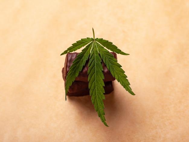 Een stapel chocolaatjes met een blad van medische marihuana, snoepjes met cannabis.