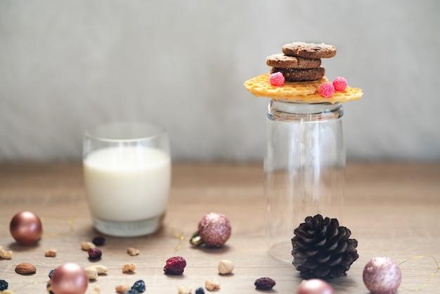 Een stapel chocoladekoekjes op knapperige wafels en een glas naast een glas melk en veel gemengde noten en rozijnen, kerstballen en dennenappel verspreid eromheen op houten tafel