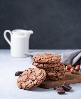 Een stapel chocoladeschilferkoekjes met chocoladeschilfers en noten met kruik op een lichte lijst. vooraanzicht en kopieerruimte