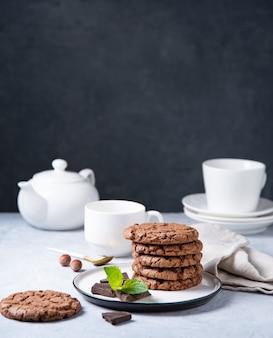 Een stapel chocoladeschilferkoekjes met chocoladeschilfers, noten en munt met kop thee en theepot op een lichte lijst. vooraanzicht en kopieerruimte