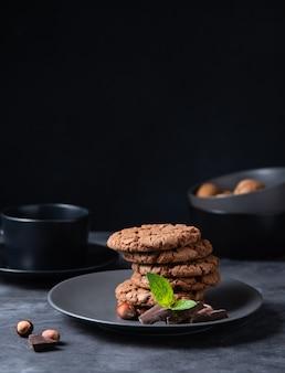 Een stapel chocoladeschilferkoekjes met chocoladeschilfers, noten en munt op een donkere lijst. vooraanzicht en kopieerruimte