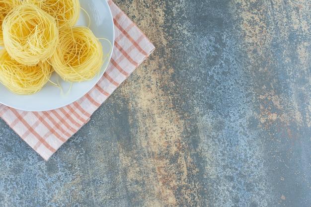 Een stapel deegwaren op de plaat op de handdoek, op de marmeren achtergrond.