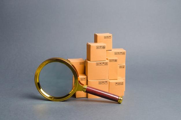 Een stapel dozen en een vergrootglas. concept zoeken naar goederen en diensten. pakketten volgen