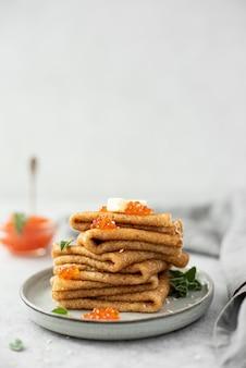 Een stapel dunne pannenkoeken met rode gezouten kaviaar en boter, close-up