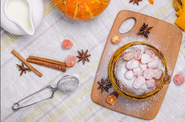 Een stapel eigengemaakte pompoenpunkcakes met poedersuiker bovenop en geconfijt kumquat.