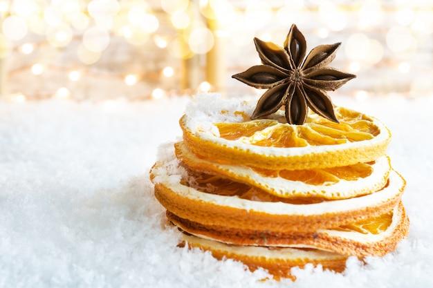 Een stapel gedroogde sinaasappelplakken en steranijs op de sneeuw.