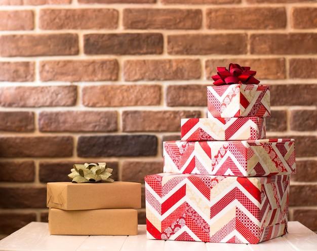 Een stapel geschenken in wit en rood inpakpapier op een bakstenen muur