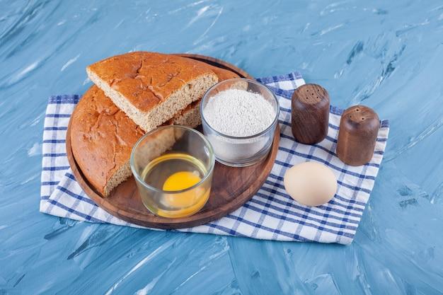 Een stapel gesneden brood op een bord naast ei en bloem op een theedoek, op het blauwe oppervlak.