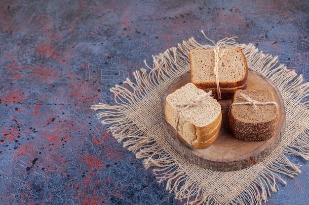 Een stapel gesneden brood op een bord op een jute servet, op het blauw.