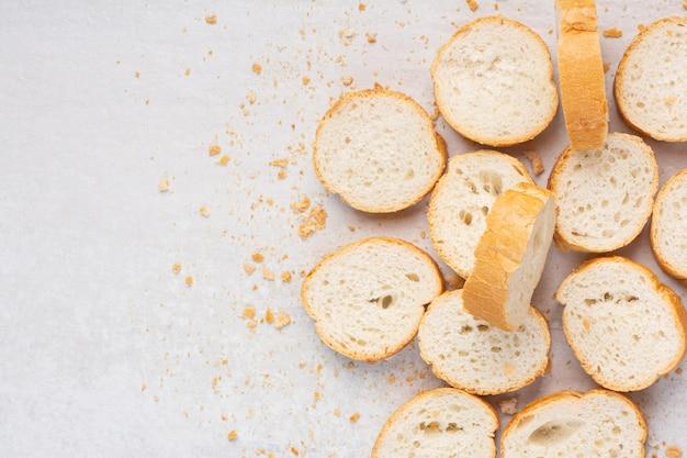 Een stapel gesneden stokbrood, op de marmeren achtergrond.