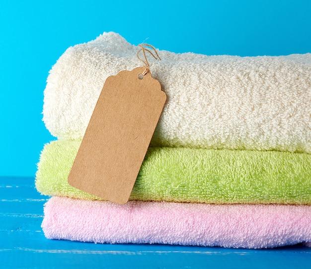Een stapel gevouwen badstof gekleurde handdoeken en een bruine papieren tag op een touw