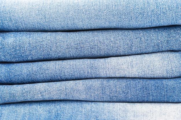 Een stapel gevouwen blauwe jeans close-up denim textuur achtergrond, een verscheidenheid aan comfortabele casual broek en kleding