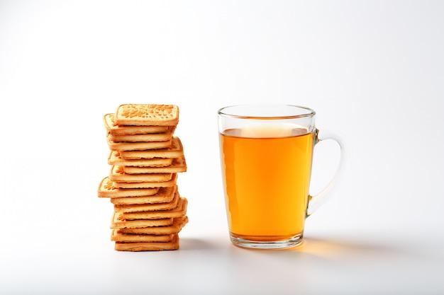 Een stapel gouden tarwekoekjes en een mok geurige groene thee op grijs